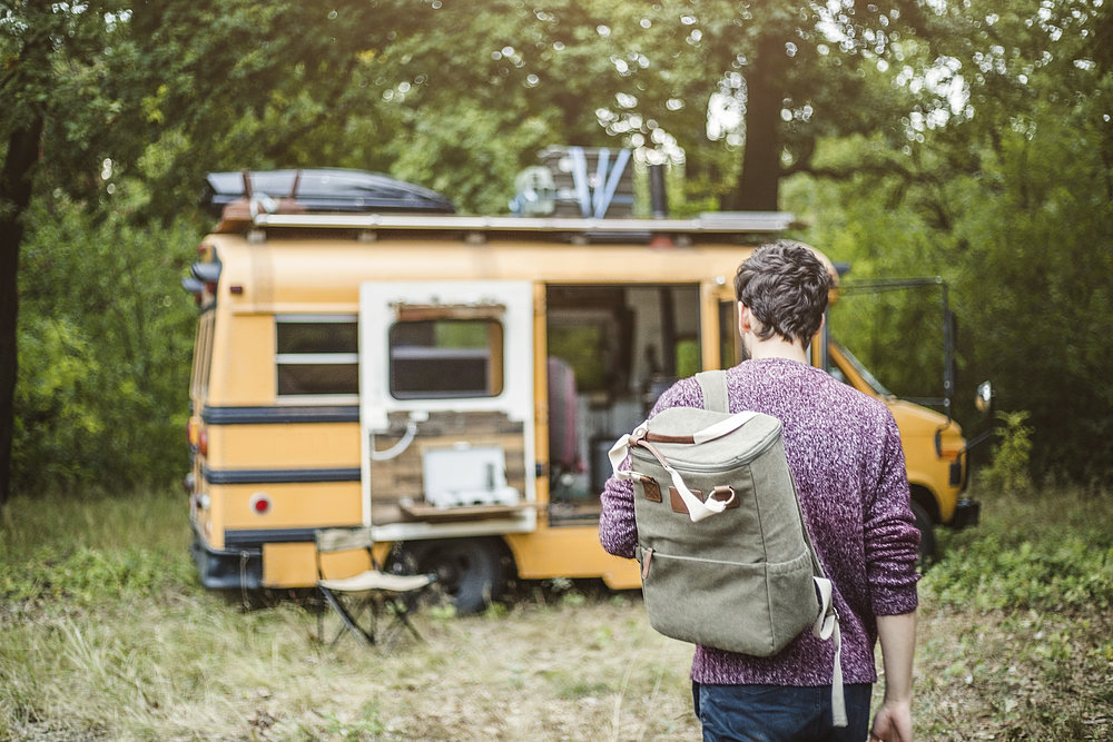 A young man with a backpack is walking towards his camping bus with which he is making a caravaning tour.
