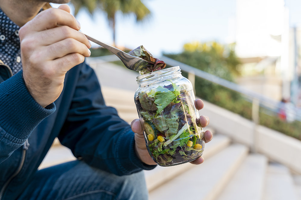 A man sits on a staircase during his lunch break and eats salad from a preserving jar for more sustainability in everyday life.
