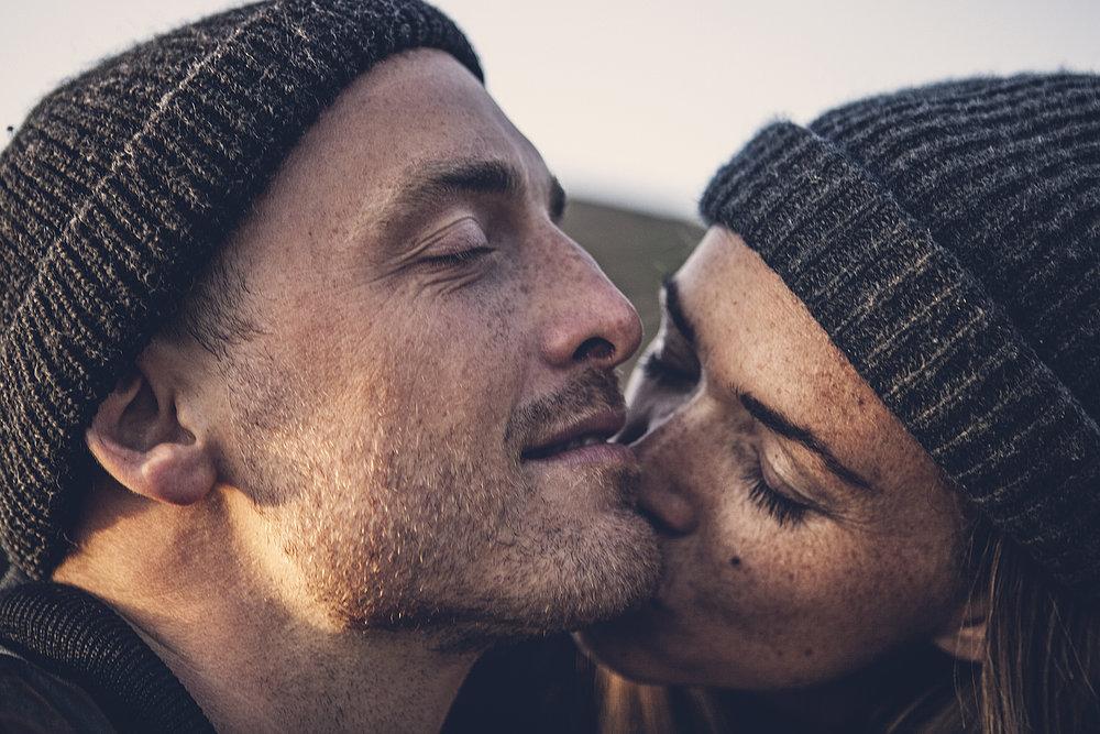 Eine Frau küsst zärtlich ihren Mann in einem Moment vertrauter Intimität.