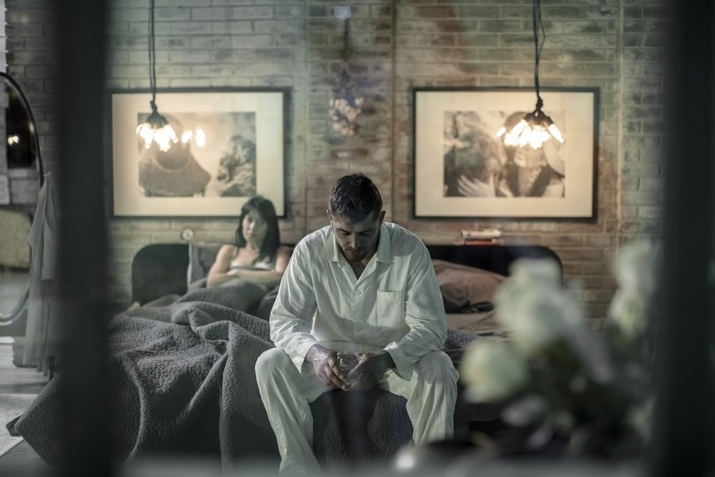 Husband and wife sit in bed with a clear distance and look unhappy.