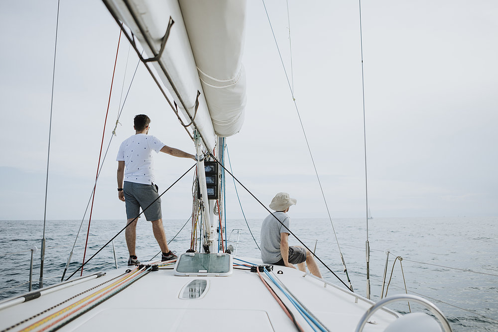 Two men stand on the deck of a sailboat overlooking the water.