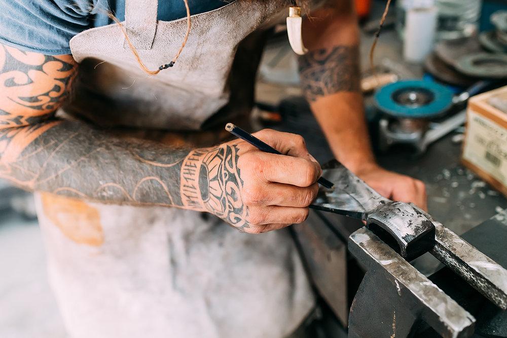 Mann stellt nach traditionellem Handwerk eine Axt her.