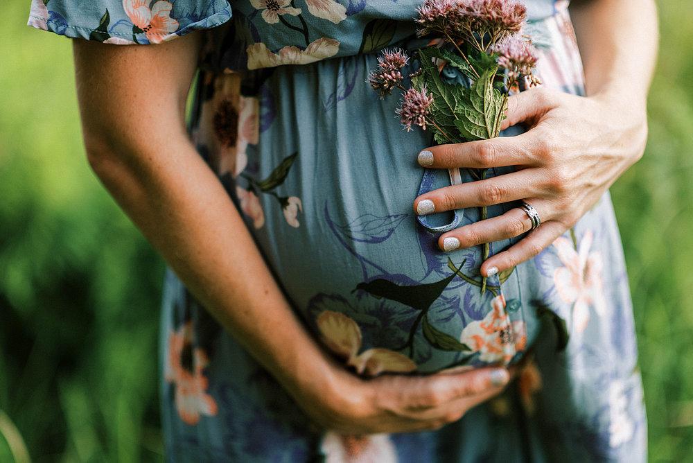 Frau in der Schwangerschaft berührt ihren Bauch.