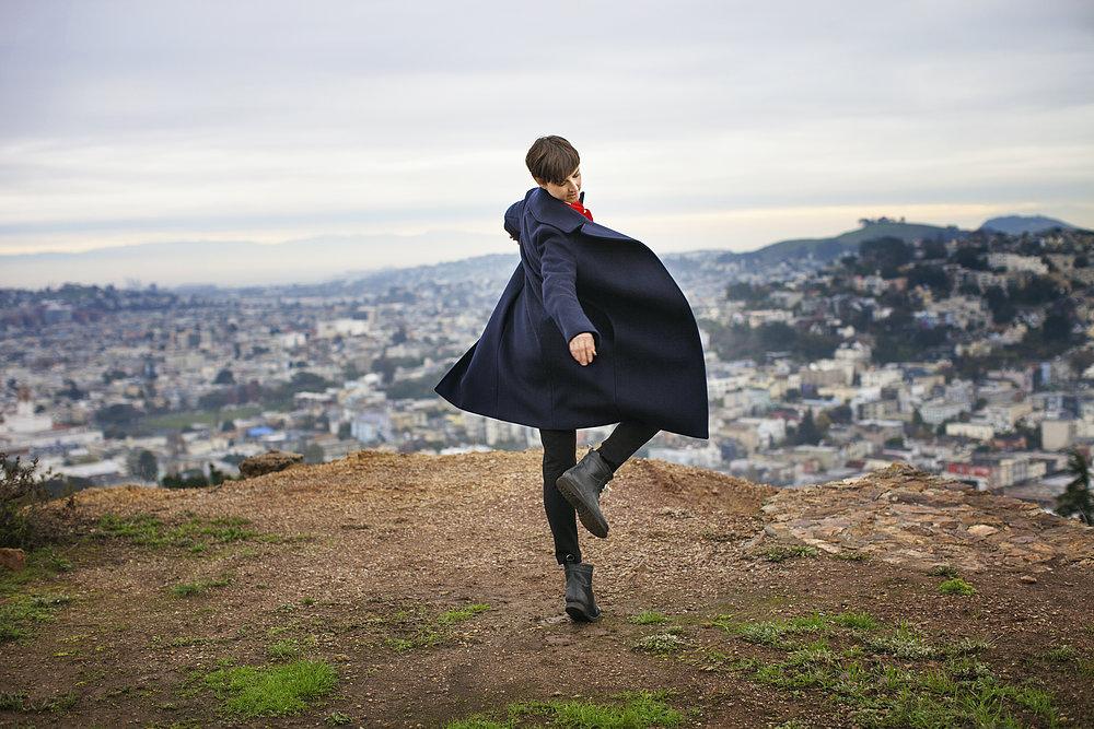 Junge Frau tanzt allein auf einem Hügel